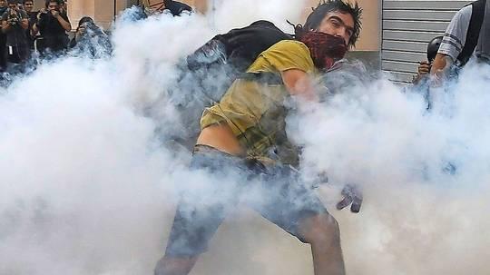 Protestwolken in Lima Ein vermummter Demonstrant wirft einen Tränengaskanister